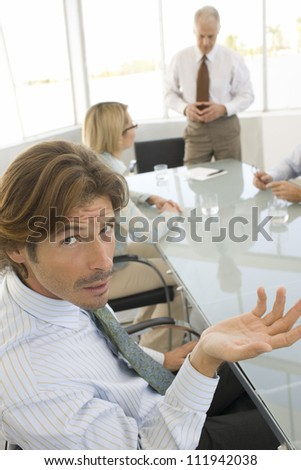 Portrait of a businessman in conference room with people in background