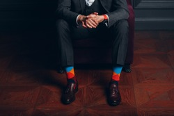 Portrait of a businessman in strict gray suit and colorful multi colored socks. Business and success concept.