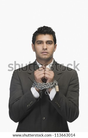 Portrait of a businessman locked with chains