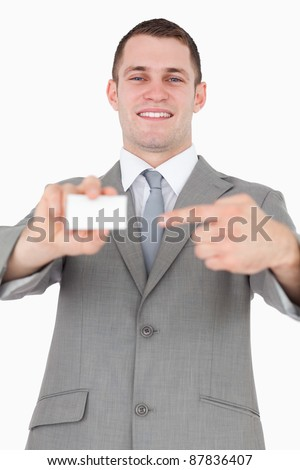 Portrait of a businessman pointing at a blank business card against a white background