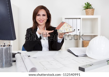 Portrait of a businessman pointing at home model with blueprints on office desk