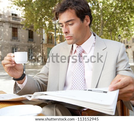 Portrait of a businessman reading the newspaper while drinking coffee in a coffee shop terrace, outdoors.