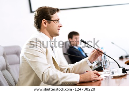 Portrait of a businessman, said into the microphone, in the background colleagues communicate with each other