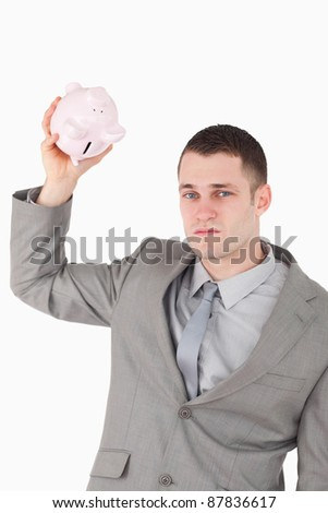 Portrait of a businessman shaking an empty piggy bank against a white background