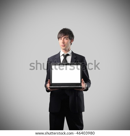 Portrait of a businessman showing the screen of a laptop
