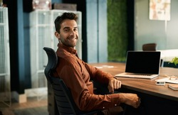 Portrait of a businessman smiling while working late on a laptop at his desk in a quiet office