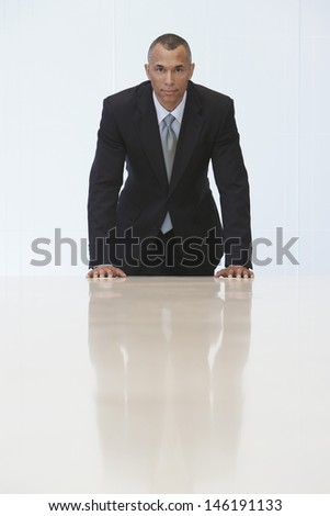 Portrait of a businessman standing at the end of conference table in office