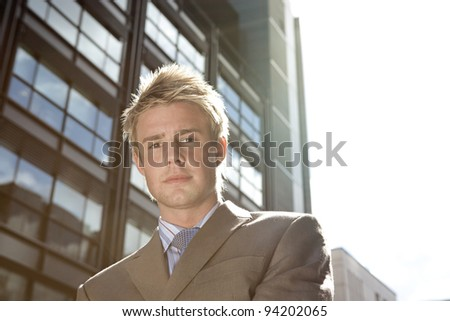 Portrait of a businessman standing by an office building in the city.