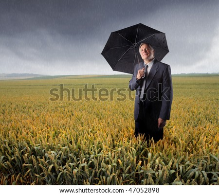 Portrait of a businessman standing in a cornfield with an open umbrella in his hand