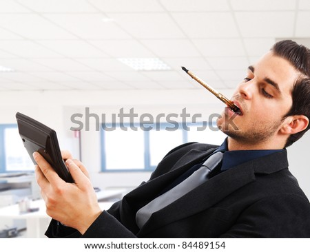 Portrait of a businessman using a calculator while sitting on a chair in his office