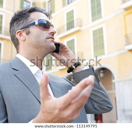 Portrait of a businessman using a smart phone to have a conversation while standing in front of classic office buildings in the city.