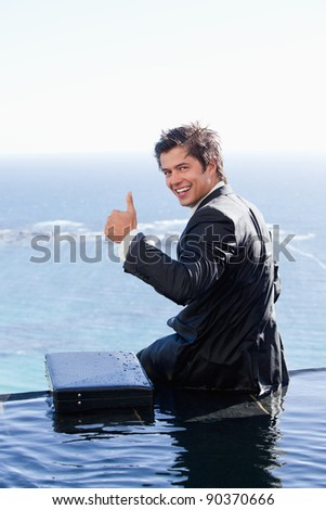 Portrait of a businessman with the thumb up in a swimming pool