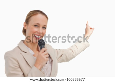 Portrait of a businesswoman in conference with a microphone against white background