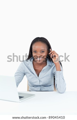 Portrait of a businesswoman making a phone call while using a notebook against a white background