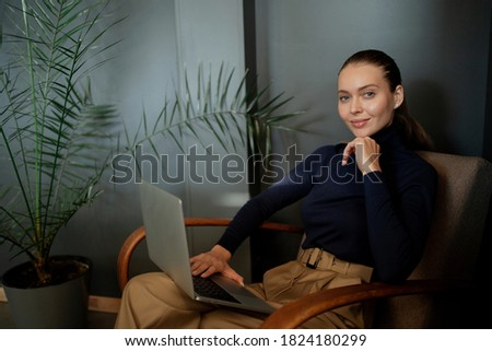 portrait of a businesswoman manager young woman sitting in an armchair and working reads an article in a laptop computer. comfortable office stylish clothes, Caucasian appearance