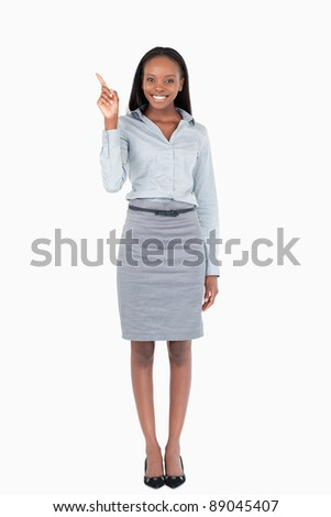 Portrait of a businesswoman pointing at something against a white background