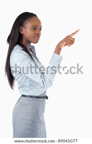 Portrait of a businesswoman pressing an invisible key against a white background