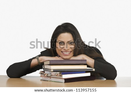 Portrait of a businesswoman resting her face on books and smiling