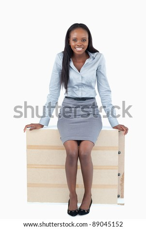 Portrait of a businesswoman sitting on a panel against a white background