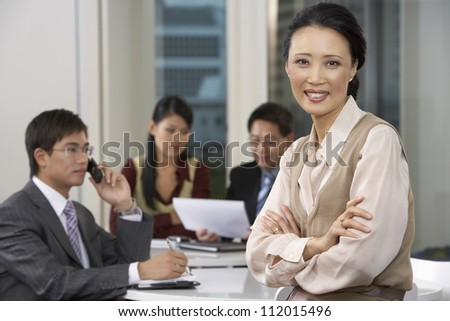 Portrait of a businesswoman standing in conference room with people in background