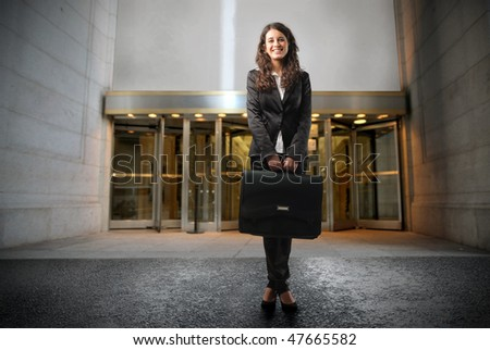 Portrait of a businesswoman standing in front of the entrance of a building