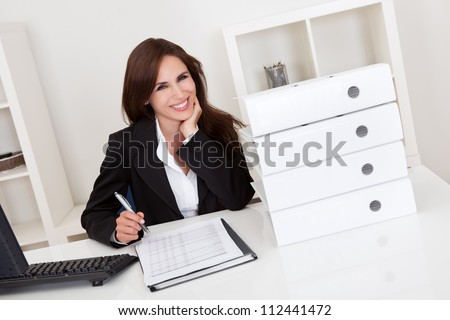 Portrait of a businesswoman with lots of paperwork at office desk