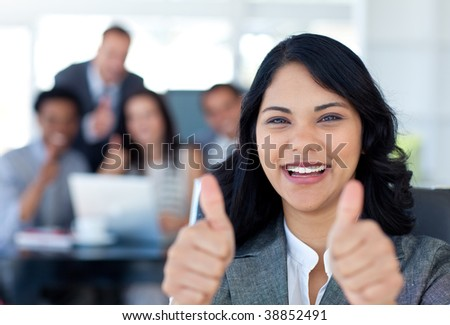 Portrait of a businesswoman with thumbs up in office with her team in the background