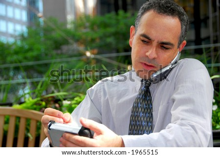 Portrait of a busy businessman in the city using pda and cell phone