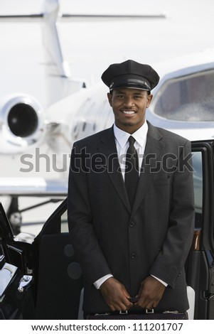 Portrait of a car driver standing by car with airplane in the background at airfield