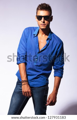portrait of a casual fashion young man wearing sunglasses posing serious on a light background