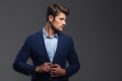 Portrait of a casual handsome man buttoning his jacket and looking away isolated on a gray background