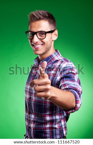 Portrait of a casual young man pointing at the camera, over green background