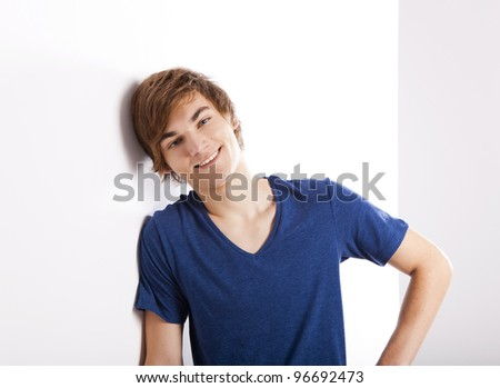 Portrait of a casual young man with a happy face, against a white wall