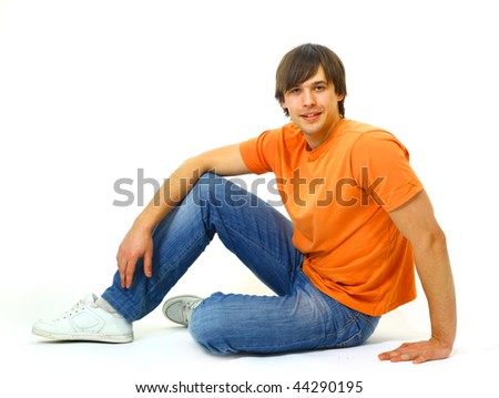 Portrait of a casual young satisfied man sitting relaxed. Isolated on white.