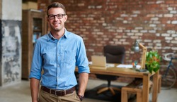 Portrait of a casually dressed young businessman wearing glasses and standing in a trendy brick walled office