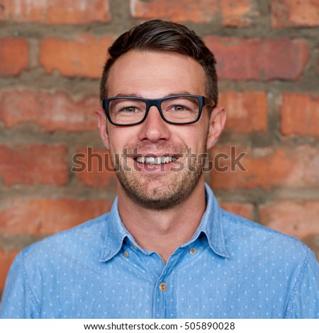 Shutterstock Portrait of a casually dressed young businessman with glasses standing against a brick wall in an office