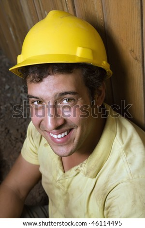 Portrait of a Caucasian male construction worker in a yellow hardhat as he rests against a fence and smiles towards the camera. Vertical shot.