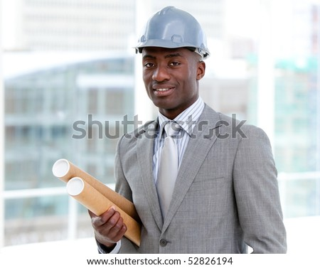 Portrait of a charismatic male architect holding blueprints in the office