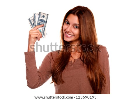 Portrait of a charming and smiling young woman with cash money against white background