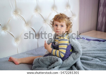 Portrait of a charming baby with golden hair and clear blue eyes. Angel face. Boy sits on the parent's bed in the bedroom. Pranks time