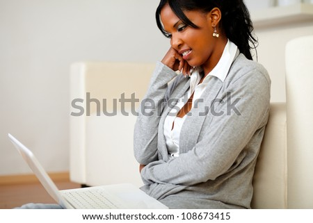 Portrait of a charming black woman sitting at home on the floor using her laptop