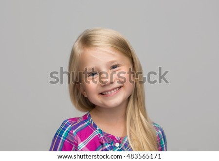 Portrait of a charming blonde little girl, isolated on gray background #483565171