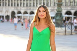Portrait of a charming Brazilian girl with a cute expression face. Tourist girl walking in St Mark's Square in Venice, Italy. She has a wonderful mood and a lovely smile.