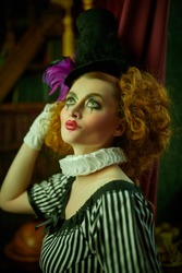 Portrait of a charming clown girl in vintage interior. Retro style.