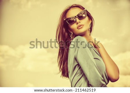 Portrait of a charming lady in beautiful elegant dress and sunglasses against the sky.