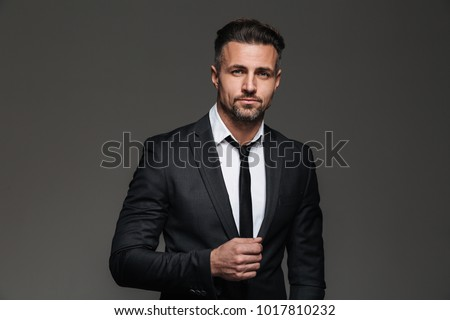Portrait of a charming mature businessman dressed in suit posing while standing and looking at camera isolated over gray background