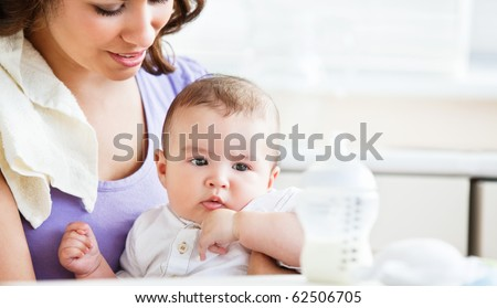 Portrait of a charming mother taking care of her adorable baby in the kitchen at home