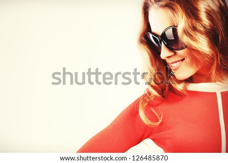 Portrait of a charming woman in red dress and sunglasses.
