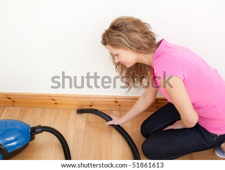 Portrait of a charming woman vacuuming at home