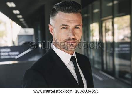 Portrait of a charming young businessman dressed in suit standing outside a glass building #1096034363